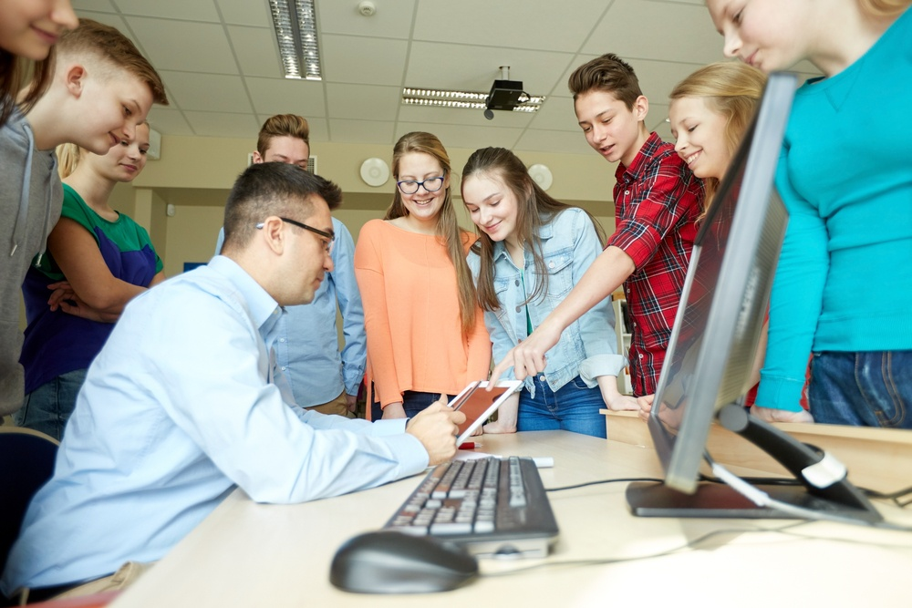 Male teacher working with group of students